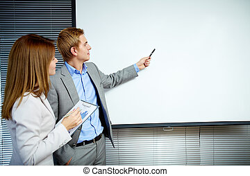 Idea - Confident businessman pointing at whiteboard while...