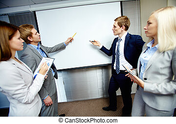 Debates - Two confident businessmen pointing at whiteboard...
