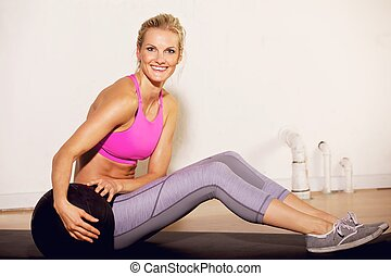 Gym Woman with a Pilates Ball - Smiling gorgeous gym woman...