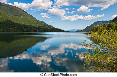 Tranquil Lake With Fluffy Cloud Reflection