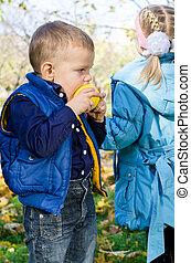 Cute little boy biting an apple