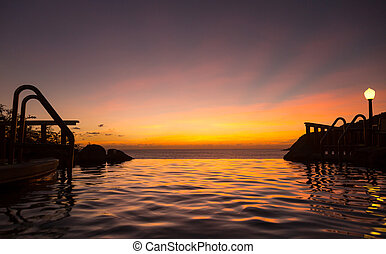 Infinity edge pool with sea underneath sunset
