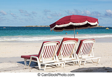 Three beach loungers and umbrella on sand - Three white...