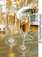 Champagne glasses on the dinner table with gift boxes
