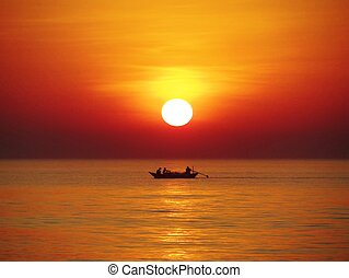Sunset with Fishing boat - Sun setting into the sea while a...