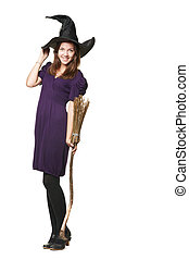 The young pretty witch with a broom and hat in a black dress...