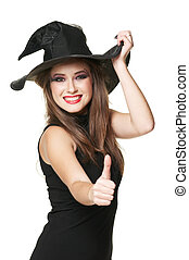 The  young smiling witch is thumb up in a black dress