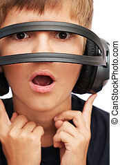 Surprised boy looking through headphones - Surprised boy in...