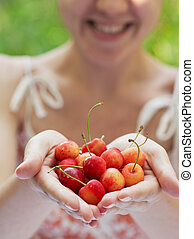 Smiling girl holding a handful of cherries