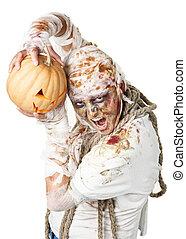 Evil mummy is holding  pumpkin in the studio