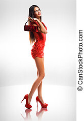 Dress up red. - Portrait of slender long legged brunette...