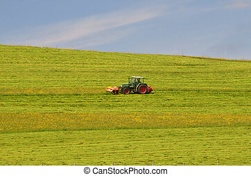 tractor cutting meadow - troctor cutting meadow during sping...