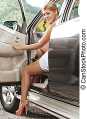 portrait of young beautiful woman stepping otta car