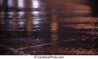 Car headlights and rain on wet pavement at night.