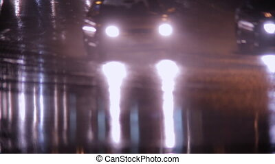 Car headlights and rain on wet pavement at night