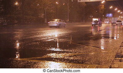 Car taillights and rain on wet pavement at night.
