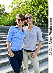 Two  beautiful woman with sunglasses on the stairs