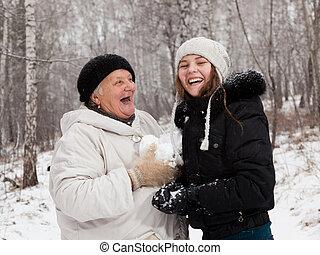 play snowballs  - Senior  woman and girl  play snowballs