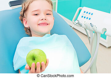 girl in the dentist's chair shows a green apple