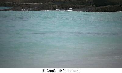 Ocean waves. - Ocean waves wash the stony shore. Rack focus.