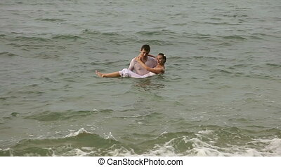 Just married - Young couple coming out of the sea