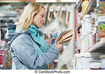 woman selecting paint at hardware store - Young woman...