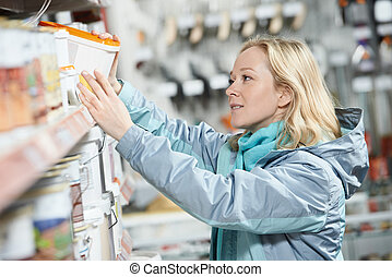 woman shopping paint at hardware store - Young woman...