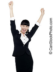 Jubilant corporate lady throwing up her hands in excitement...