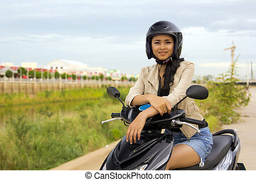 sexy asian girl with mini skirt, helmet, motorcycle in...
