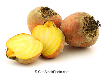 two yellow beetroots and a cut one on a white background