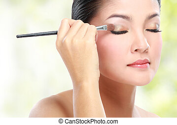 eyelid make up - Beautiful young woman applying eyelid make...