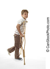 Wincing injured boy using crutches - An injured boy with...