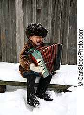 boy with accordion under snowfall