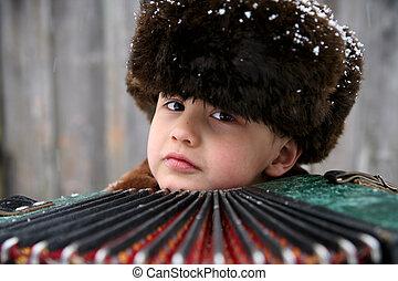 boy with accordion under snowfall