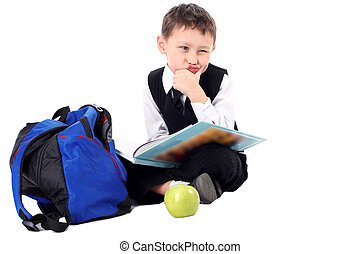 hard time in learning - schoolboy with book and apple...