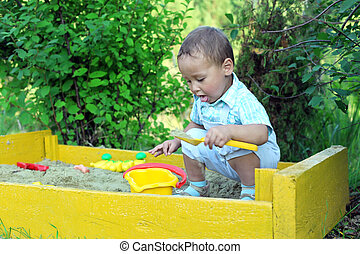baby plays with toys in sandbox