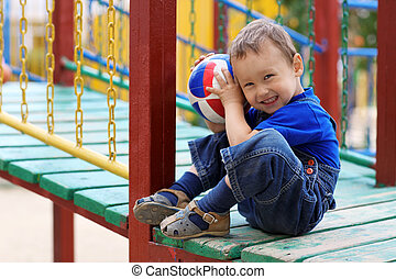 Young boy with ball smiling