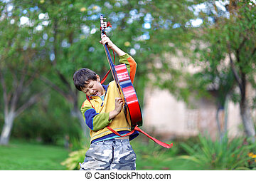 Music student playing the guitar and sing outdoors