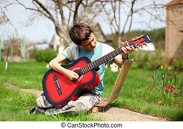 Music student playing the guitar outdoors