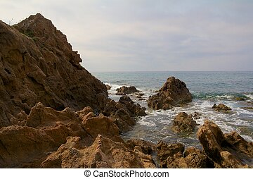 View on the Mediterranean Sea with harsh rocks in the foreground