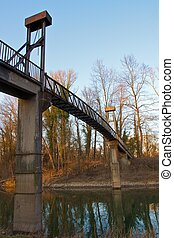 Metal bridge spanning a small river in the famous Rheinauen nature reserve at the River Rhine, Karlsruhe, Germany