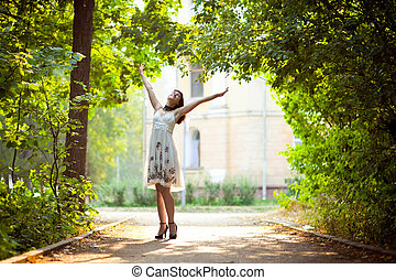Enjoying the nature Young woman arms raised enjoying the...