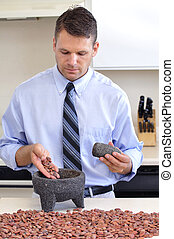 Cocoa beans - Man preparing to grind raw cocoa beans in...