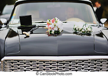 retro car decorated for wedding with a top hat on it