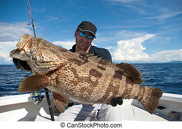 Grouper fish - Happy  fisherman holding a grouper