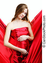 a beautiful young pregnant woman in red on a white background