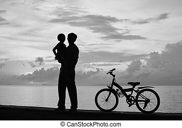 Family - Biker family silhouette at the beach at sunset