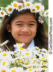 Beautiful little girl with crown of daisies