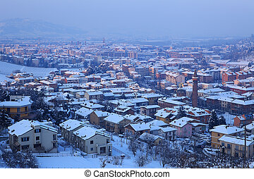 Town covered by snow at evening. Alba, Italy.