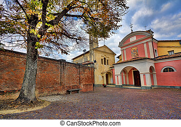 Small cobbled courtyard. Barolo, Italy. - Big tree on small...